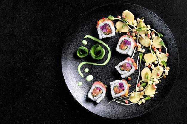 Set di rotoli di sushi servito sulla banda nera su sfondo scuro.concetto di design.vista dall'alto