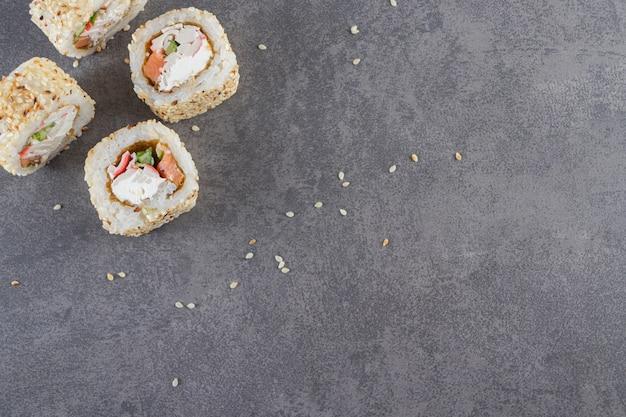 Rotoli di sushi, salsa di soia, wasabi e zenzero sott'aceto su fondo di pietra.