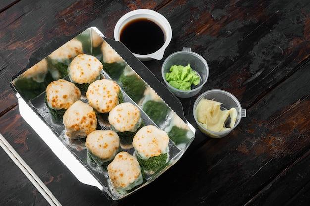 Rotoli di sushi in un set di contenitori da asporto, su un vecchio tavolo di legno scuro