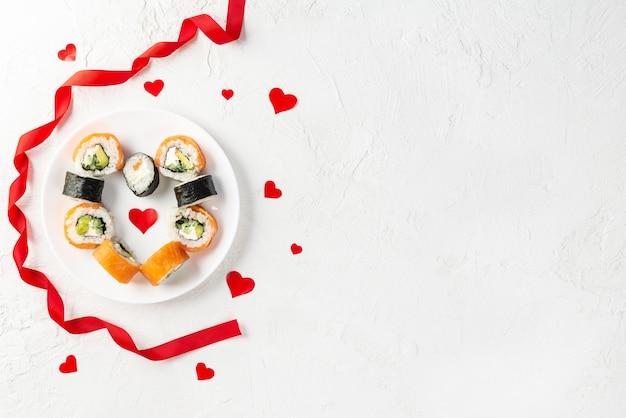 Rotoli di sushi per san valentino con cuori rossi e nastro su un piatto bianco.
