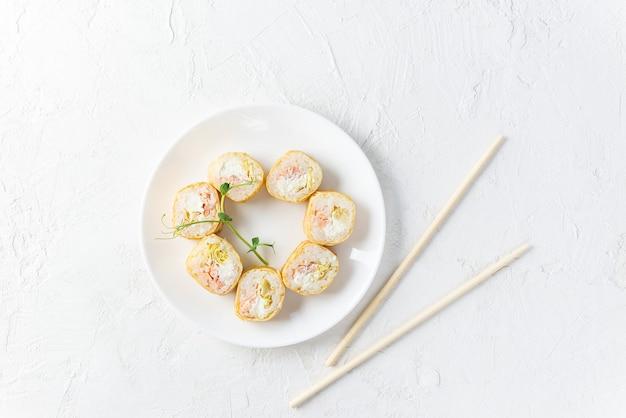 Sushi rotoli in un piatto bianco con le bacchette.