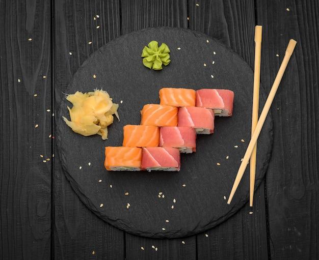 Rotoli di sushi con formaggio philadelphia, salmone e tonno sul nero