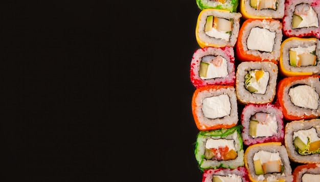 Rotoli di sushi con il cetriolo e l'avocado con il fondo del confine dell'alimento delle verdure crude