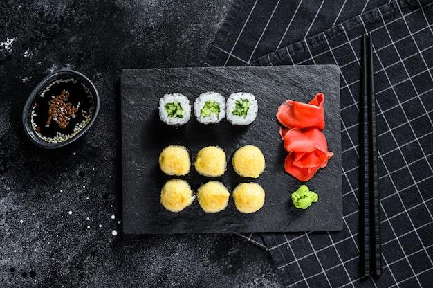 Rotoli di sushi con cetriolo, salmone e gamberi su un vassoio di pietra.