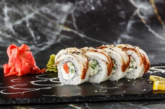 Sushi rolls con cetriolo, pomodoro, anguilla e crema di formaggio all'interno su ardesia nera isolato su sfondo di marmo nero. philadelphia unagi roll. menu di sushi. foto orizzontale.