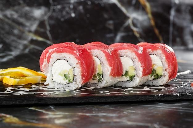 Sushi rolls con cetriolo, tonno e crema di formaggio all'interno su ardesia nera isolato su sfondo di marmo nero. sushi del rotolo di filadelfia con gambero. menu di sushi. foto orizzontale.