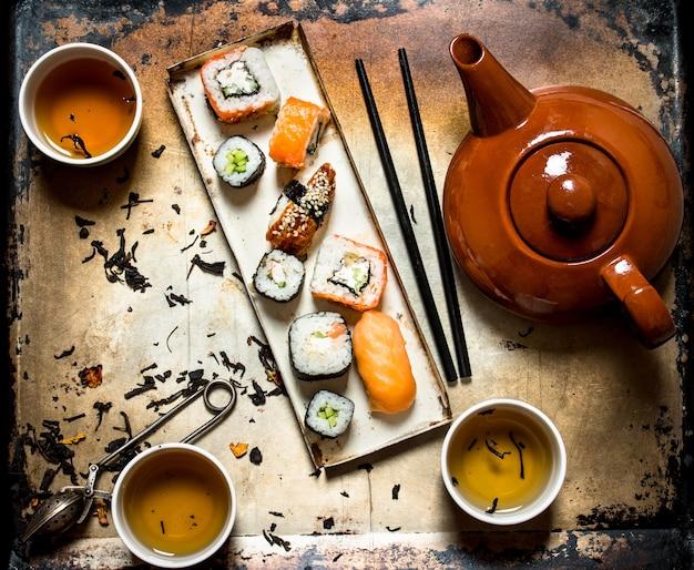 Sushi e panini con tisana su un vecchio fondo rustico.