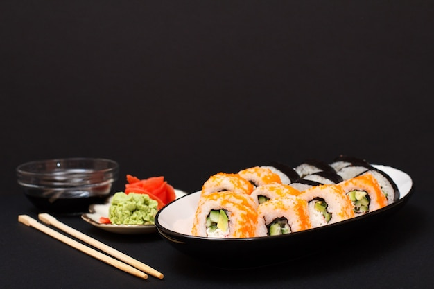 Rotoli di sushi con nori, riso, pezzi di avocado, cetriolo, uova di pesce volante su piatto di ceramica. piatto con zenzero sottaceto rosso e wasabi. ciotola con salsa di soia e bastoncini di legno. sfondo nero.