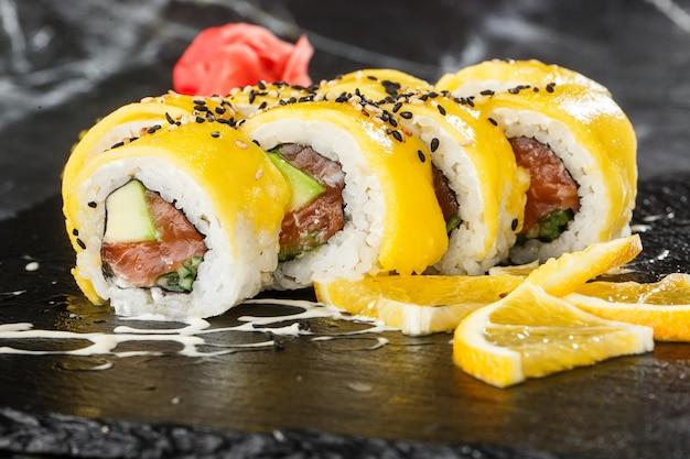 Sushi rolls con salmone, avocado, omelette all'interno e mango in cima. sushi rolls con salmone su fondo di marmo nero. menu di sushi. cibo giapponese. foto orizzontale.