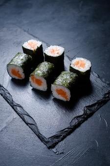 Rotoli di sushi con salmone ricoperto di nori su sfondo scuro. menu ristorante di cucina orientale. cibo tradizionale delizioso