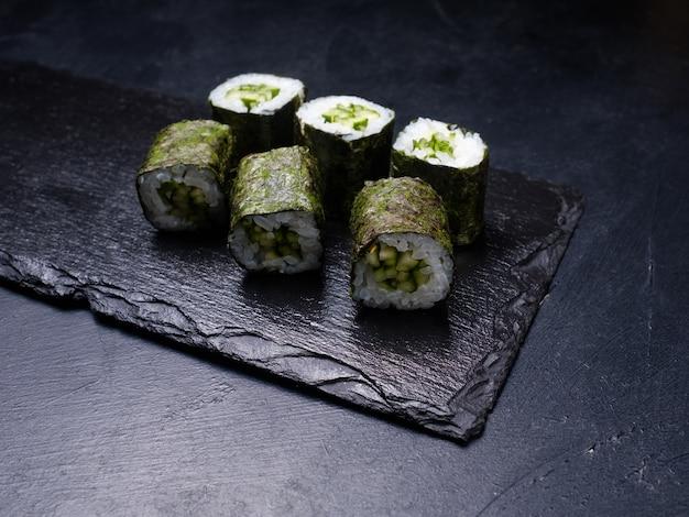Rotoli di sushi con salmone ricoperto di nori su sfondo scuro. cucina orientale e concetto di cibo tradizionale