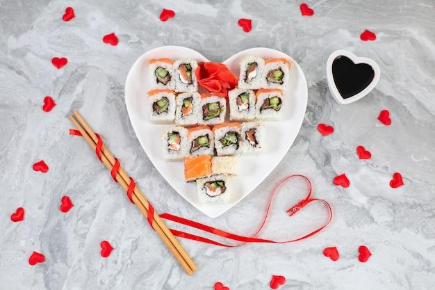 Rotoli di sushi con salmone su piatto bianco a forma di cuore e bastoncini di sushi in legno tra cuori di coriandoli rossi