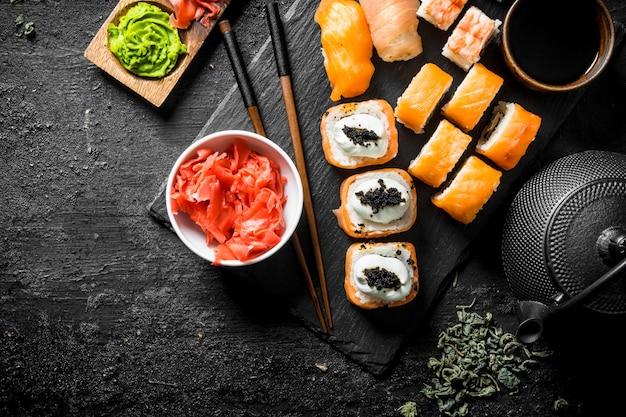 Rotoli di sushi con gamberi salmonnd su supporto di pietra sul tavolo rustico nero