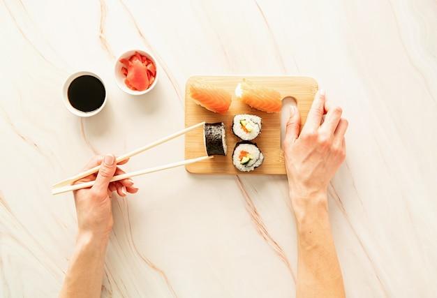 Sushi salmone impostato sul tagliere di legno. mano della donna che tiene il rotolo di sushi con le bacchette. lay piatto