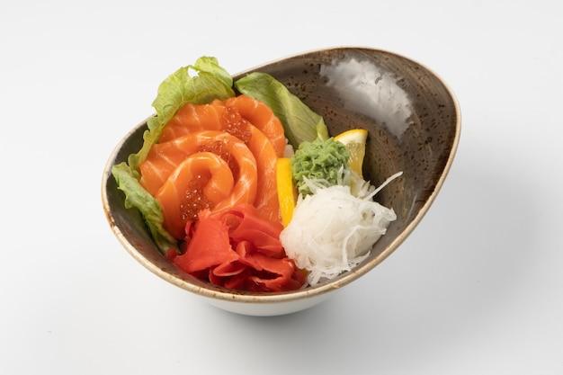 Sushi sashimi. fette di salmone con caviale rosso, daikon ibir di ravanello, wasabi, lattuga e spicchio di limone su un pad di riso
