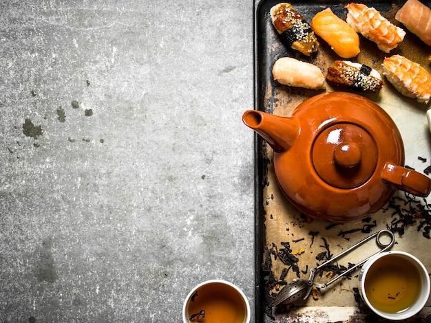 Sushi frutti di mare e tisane su un vecchio vassoio.