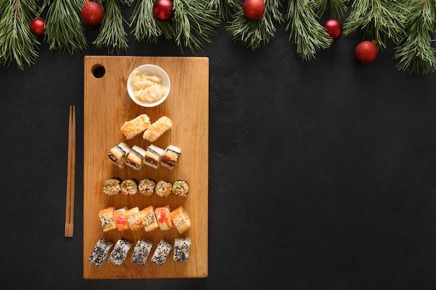 Set di sushi come albero di natale servito sul tagliere di legno come decorazione di natale su sfondo nero. vista dall'alto. spazio per il testo. stile piatto.