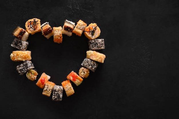 Sushi impostato come cuore su sfondo nero. concetto di cibo di san valentino. vista dall'alto. spazio per il testo. stile piatto.