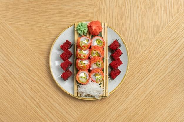 Sushi set di diversi rotoli con tonno, salmone, gamberetti, uova di pesce volante tobiko, zenzero, ravanello daikon, riso nero con seppie e cherinles al wasabi.