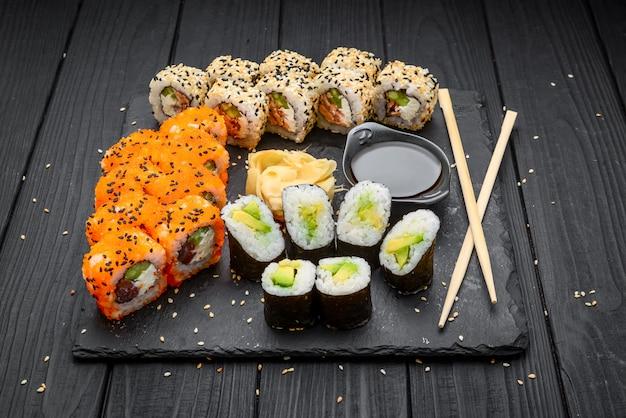 Set di sushi nigiri e involtini di sushi serviti su ardesia di pietra nera