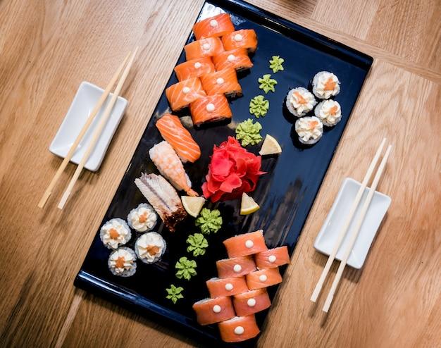 Set di sushi rotoli con salmone, anguilla e caviale rosso su un piatto di legno.