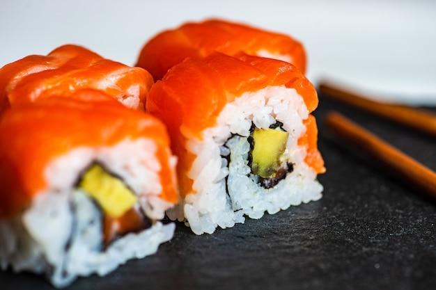 Sushi set sashimi e involtini di sushi serviti su ardesia di pietra