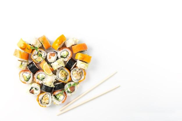 Sushi impostato a forma di cuore su un piatto bianco, il giorno di san valentino.