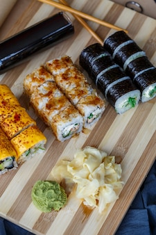 Set sushi con diversi tipi di panini e sashimi a base di anguilla, salmone, tonno, gamberi, caviale rosso e uova di pesce volante tobiko. cibo e piatti panasiatici e asiatici su un tavolo da cucina in cemento nero.