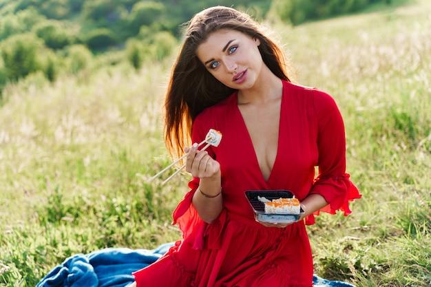Sushi e ragazza sexy con gli occhi azzurri al picnic. consegna del cibo dal ristorante giapponese.