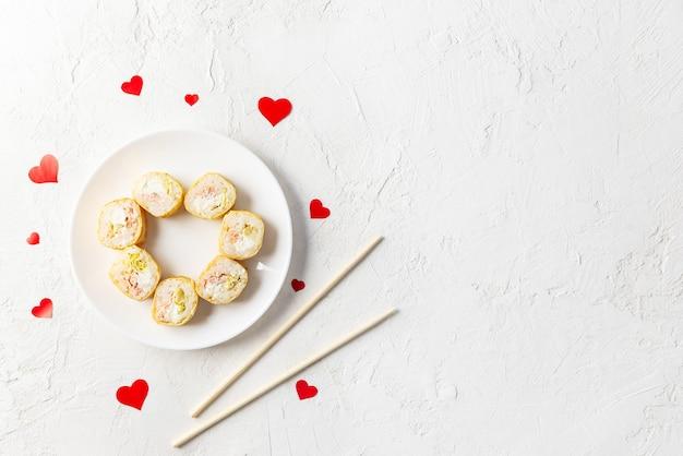Sushi per san valentino con cuori rossi e bacchette su un piatto bianco.