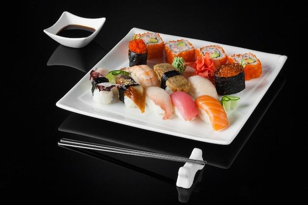 Sushi in un piatto bianco con salsa pentola e bacchette su sfondo nero con riflesso