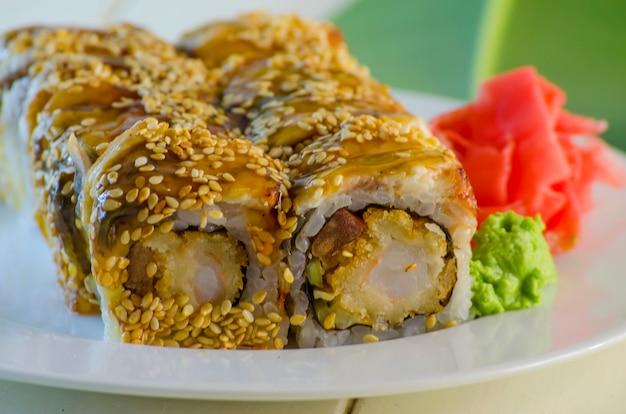 Sushi con tempuro di anguilla e gamberi su un piatto e uno sfondo bianco