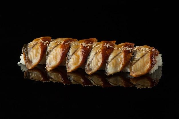 Sushi con riso e semi di sesamo su sfondo scuro con riflesso
