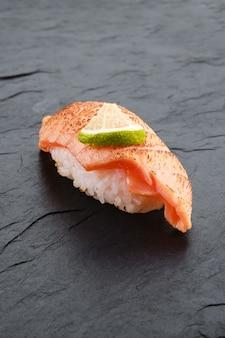 Sushi con salmone scottato su lastra di ardesia