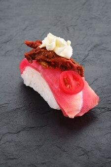 Sushi con tonno, pomodori secchi e crema di formaggio su lastra di ardesia