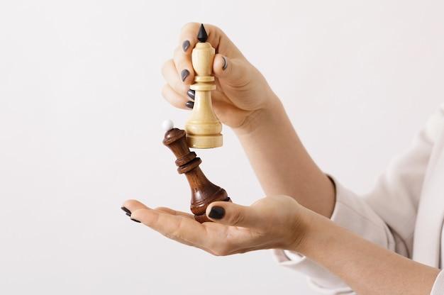 Susinesswoman che tiene la figura degli scacchi nelle sue mani. mosse intelligenti e strategia nel mondo degli affari. Foto Premium