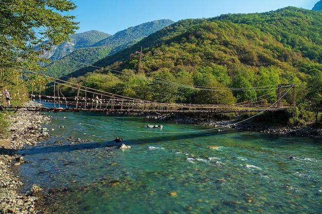 Ponte sospeso sul fiume di montagna bzyb. abkhazia, la strada per il lago ritsa.
