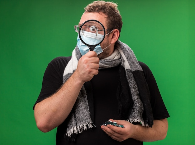 Sospetto uomo malato di mezza età che indossa maschera medica e sciarpa con pillole che guardano la telecamera con lente d'ingrandimento