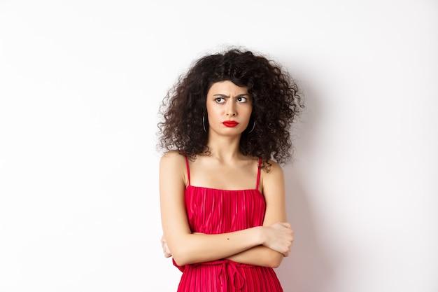 Donna elegante sospettosa e riluttante, vestita di rosso e accigliata, guardando a sinistra con incredulità, in piedi su sfondo bianco.