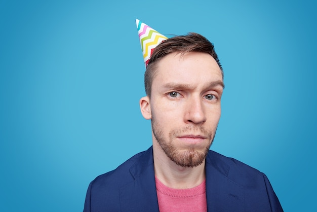 Giovane sospettoso in giacca, pullover e berretto da compleanno che ti guarda da solo