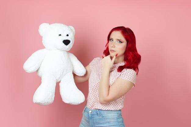 Sospettosa giovane donna con i capelli rossi tiene un grande orsacchiotto bianco e si strofina il mento con la mano
