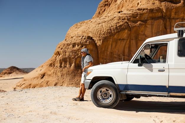 Spedizione in auto suv in un deserto di pietra dell'egitto. paesaggio di montagna con fuoristrada.