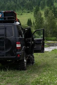 Suv con porte aperte sullo sfondo delle montagne. macchina da spedizione per viaggiare