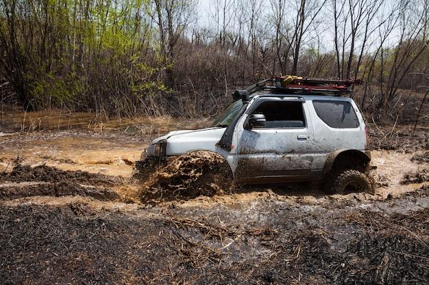 Suzuki jimny attraversa un ostacolo d'acqua nella foresta primaverile