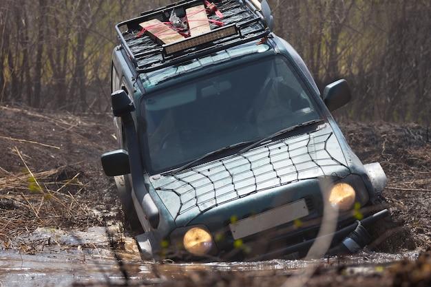 Suzuki jimny che attraversa un ostacolo d'acqua o una palude