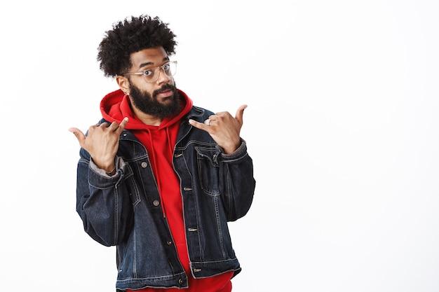 Swag nel sangue. ritratto di cool ed elegante bella fiducioso maschio afroamericano che agisce come star e persona popolare che mostra gesto yolo e guardando sicuro di sé in telecamera sul muro grigio