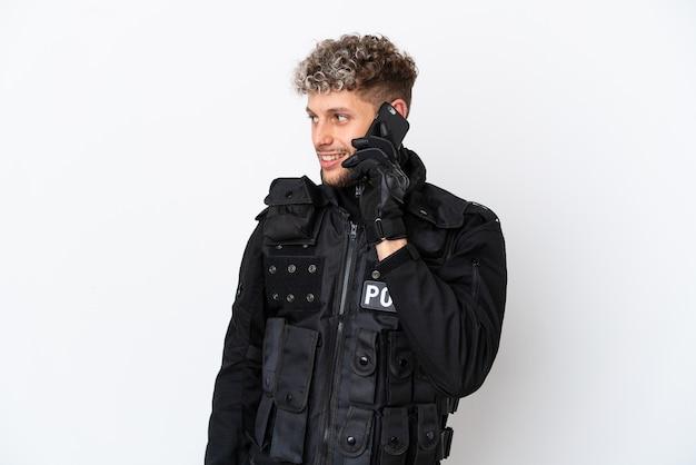 Swat uomo caucasico isolato su sfondo bianco mantenendo una conversazione con il telefono cellulare con qualcuno