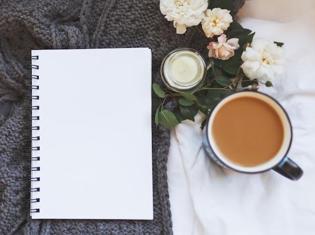 Maglione e tazza di caffè con taccuino, candele, rose e vestiti grigi per maglieria su uno sfondo di foglio bianco stropicciato. accogliente concetto autunnale o invernale. copia spazio