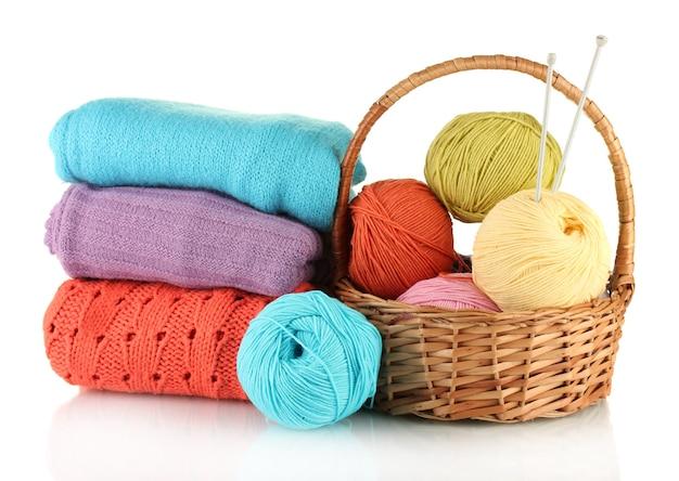 Maglioni e gomitoli di lana isolati su bianco