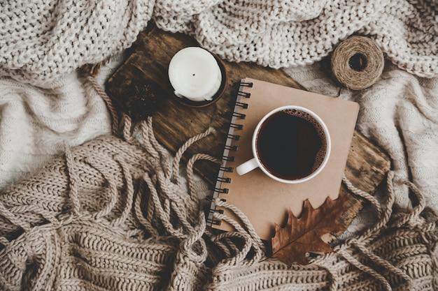 Maglioni e tazza di tè con notebook, candele e maglieria